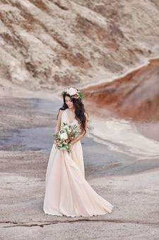 머리에 꽃다발을 들고 손에 아름다운 꽃 한 다발을 들고 산 배경을 걷는 여성. 바람에 펄럭이는 가벼운 여름 롱원피스