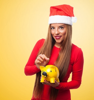 Woman with a yellow piggy bank and santa's hat