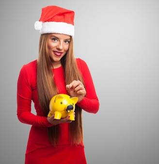 Woman with a yellow piggy bank in a gray background