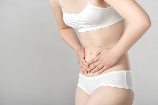 Woman with abdominal pain on a gray