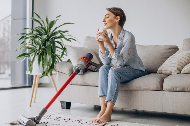 Женщина с аккумуляторным пылесосом пьет кофе