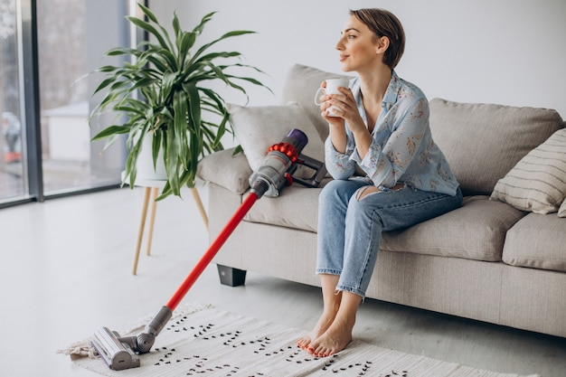 Woman with accumulator vacuum cleaner drinking coffee