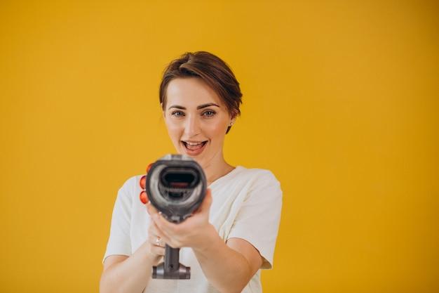黄色の背景にアキュムレータ掃除機を持つ女性