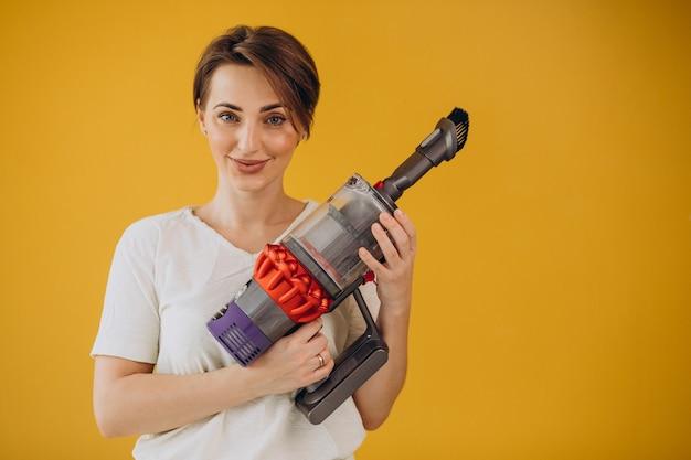 Женщина с аккумуляторным пылесосом на желтом фоне