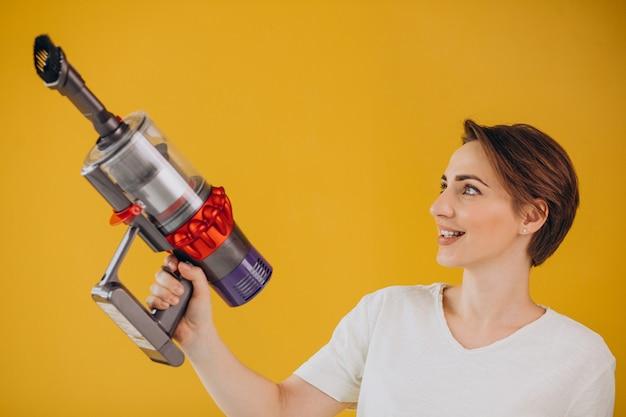 Donna con aspirapolvere ad accumulatore su sfondo giallo