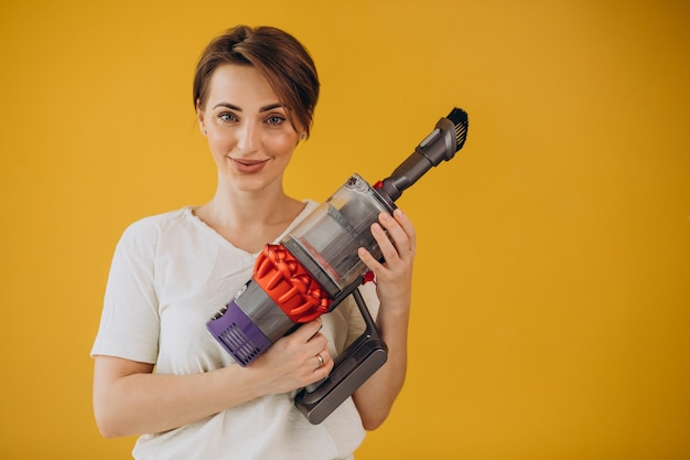 Woman with accumulator vacuum cleaner on yellow background