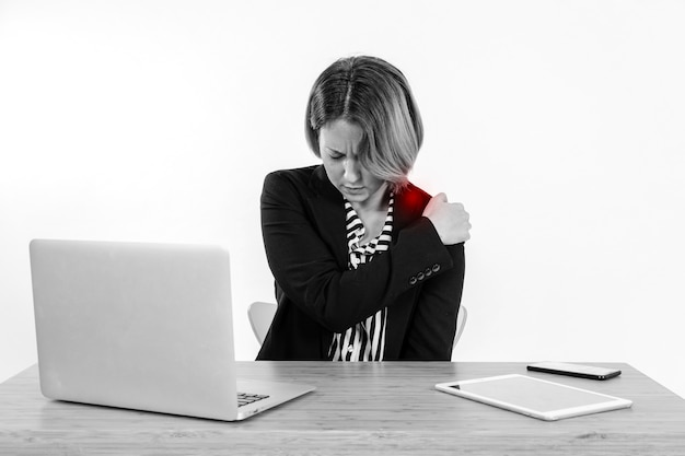 Woman with aching shoulder in office
