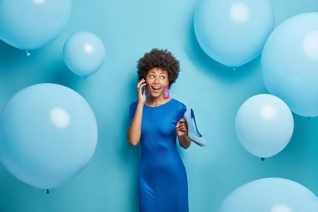 축제 복장을 입은 아프로 머리를 가진 여자가 스마트 폰을 통해 누군가에게 전화를 걸어 파란색에 회의 포즈를 준비합니다.