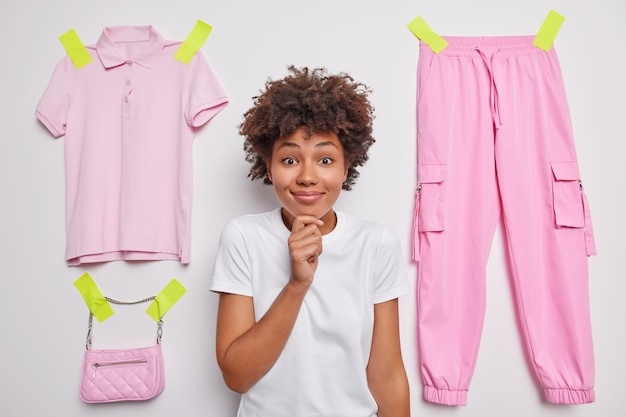 Woman with afro hair holds chin looks happily at camera wears casual t shirt poses agaist white with plastered items of clothes thinks about donation cleans out wardrobe