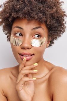 아프로 머리를 한 여성이 턱에 손을 대고 수심에 찬 시선으로 미용 절차를 받고 있습니다. 피부에 수분을 공급하기 위해 눈 아래 패치를 적용합니다.