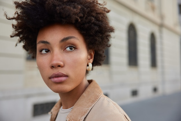 Женщина с афро-волосами внимательно смотрит куда-то вдаль, позирует на старинном здании с копией пространства для информации