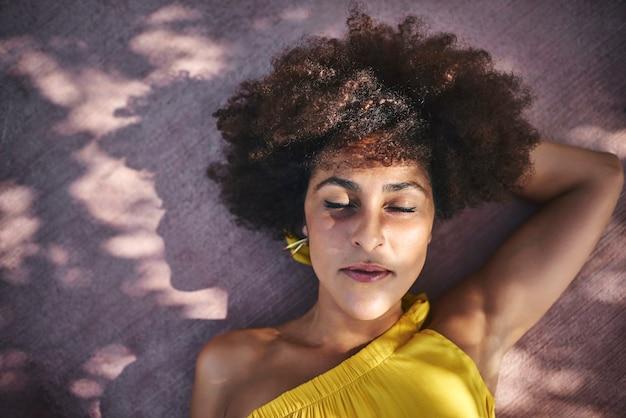 床に横たわっているアフロ髪の女性