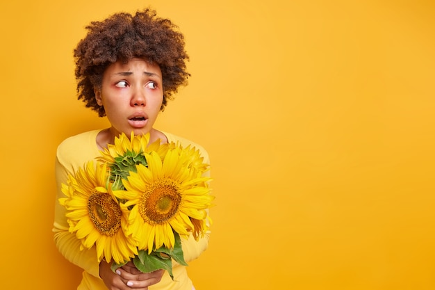 Woman with afro hair red eyes looks away has frightened expression holds bouquet of sunflowers suffers from seasonal allergy poses on yellow