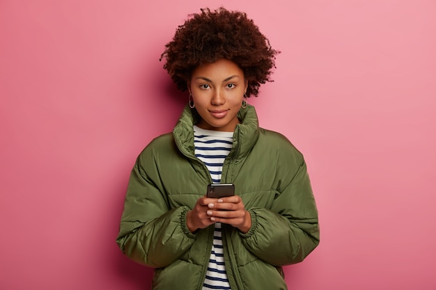 Donna con taglio di capelli afro, indossa maglione a righe e giacca invernale