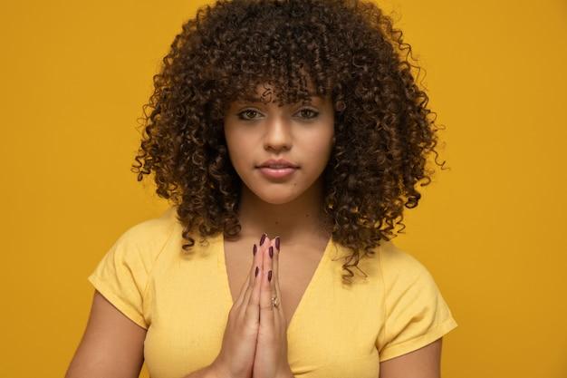 アフロの髪型と黄色のトップを持つ女性