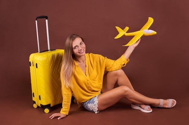 Женщина с самолетом в руке сидит на желтом чемодане