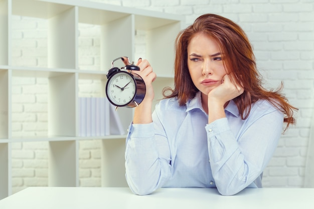 Woman with alarm clock at table in office