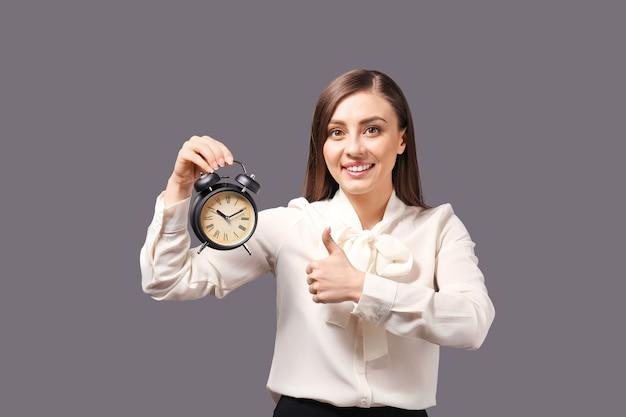 알람 시계를 가진 여자입니다. 시간 관리 개념