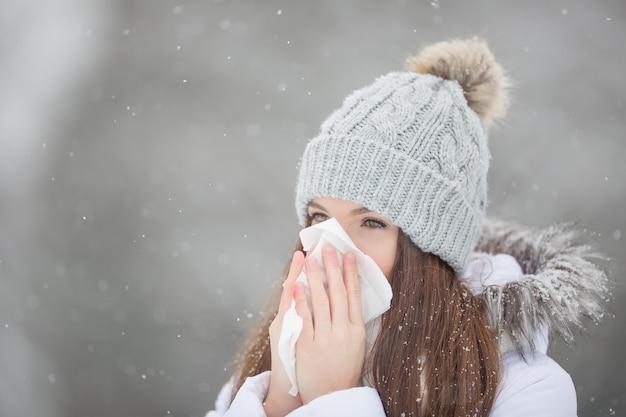 Женщина с симптомом аллергии сморкается