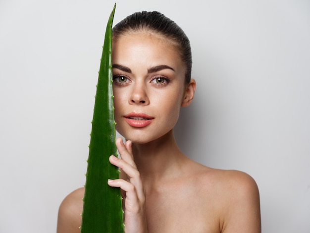 Woman with aloe leaf on light background portrait cropped view model