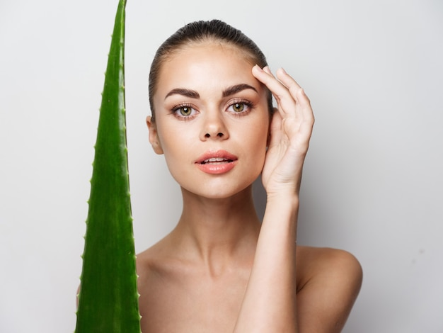 Woman with aloe leaf on a light background touches her face with her hand cosmetology