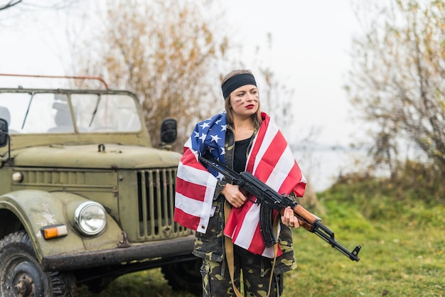 軍用車の近くにアメリカの国旗とライフルを持つ女性