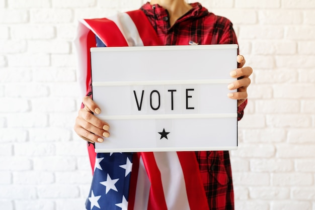 Woman with american flag holding lightbox with the word vote on white brick background