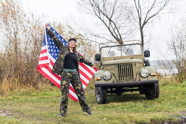 Woman with american flag and military car