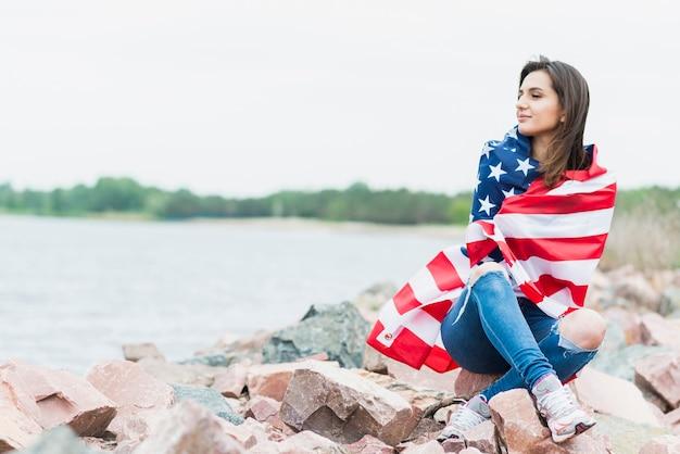 Женщина с американским флагом рядом с морем
