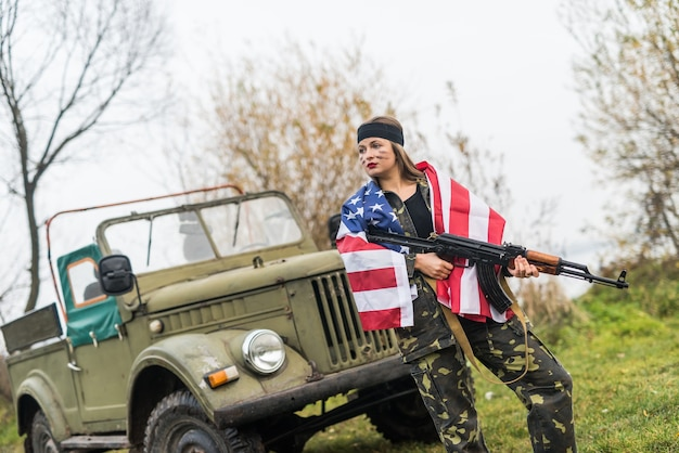 Woman with american flag and rifle near military car