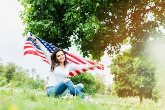 Woman with american flag sitting under tree