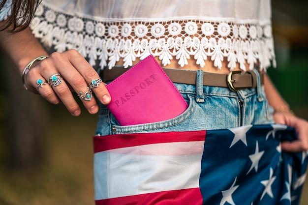 アメリカの国旗とジーンズのポケットにパスポートを持つ女性