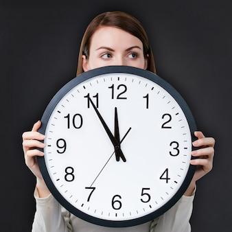 Женщина с офисными часами на фоне классной доски