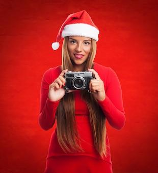 Женщина со старой камерой в красном фоне