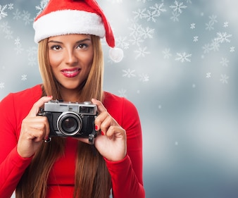 Woman with an old camera in a snowflakes background