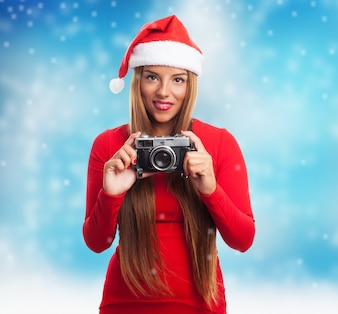 Woman with an old camera while snowing