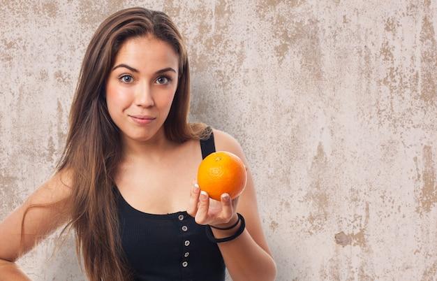 彼女の手でオレンジ色を持つ女性