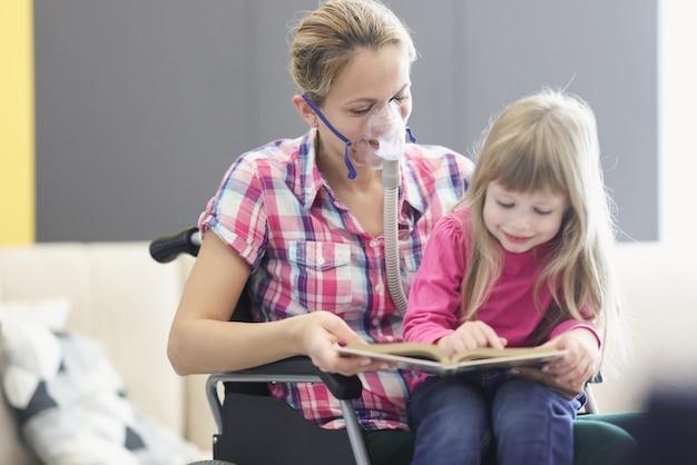 산소 마스크와 휠체어에 여자는 어린 소녀와 함께 책을 읽고