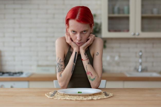 Женщина с анорексией. худенькая женщина, страдающая анорексией, сидит на кухне возле тарелки с горошком