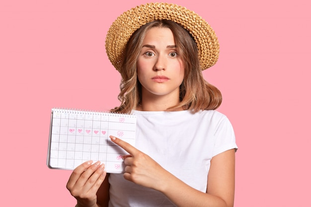 Woman with appealing look, holds periods calendar for checking menstruation days, points with fore finger