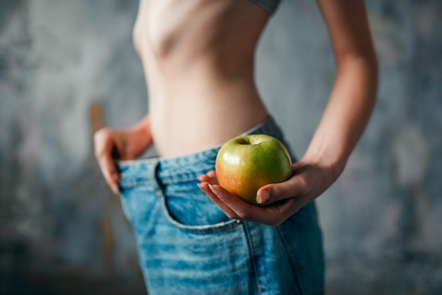 Woman with apple in hand tries on big size jeans, weight loss. fat or calories burning concept, hard dieting