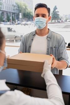 男性のお客様にパックテイクアウト食品を提供するエプロンを持つ女性