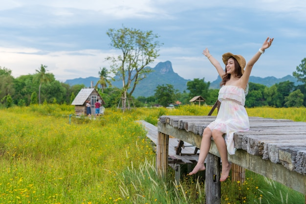 Woman with arm raised on wooden bridge with yellow cosmos flower field