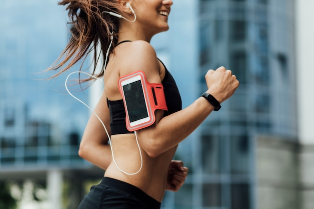 Woman with armband and headphones running