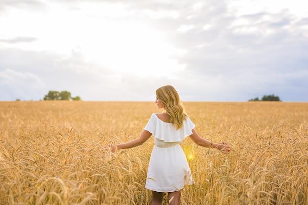 Женщина с раскинутыми руками в пшеничном поле.