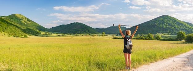 自然公園の景色を眺めながら腕を伸ばした女性