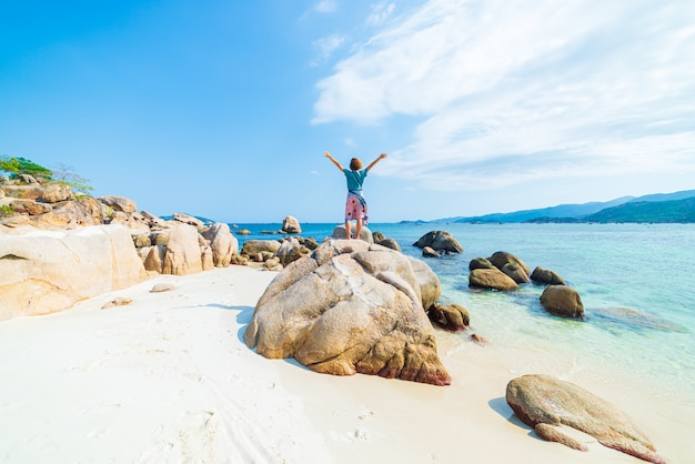 Женщина с оружиями протягивала смотреть стоящ на валуне в тропическом пляже. вьетнамское туристическое направление, провинция фу йен, между данангом и нячанг. великолепный песчаный пляж