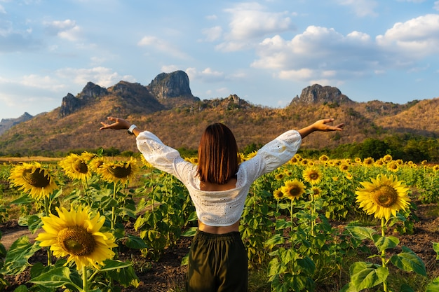 Woman with arms raised in sunflower field at kao jeen lae in lopburi, thailand