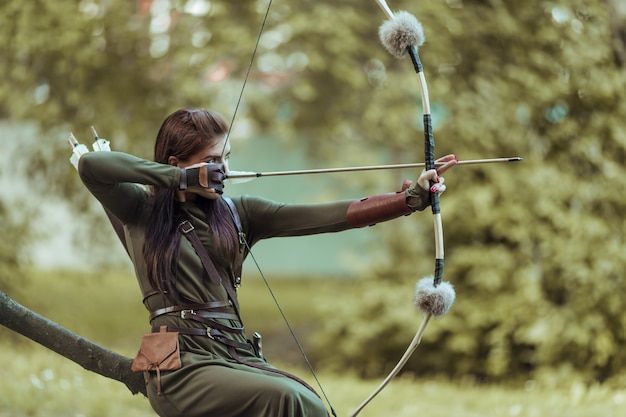 Woman with arrows and bow sits on a fallen tree and takes aim at a target