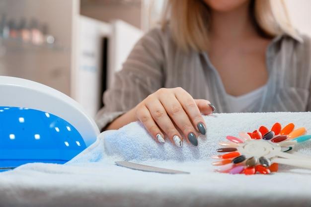 Женщина с искусственными акриловыми ногтями подбирает новый цвет лака во время процедуры маникюра. процесс маникюра в салоне красоты. гигиена красоты рук в маникюрном салоне.